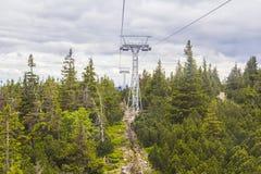 Kabelbahn, die zu den Berg im Tschechische Republik SnÄ-› Å ¾ Ka auf dem Hintergrund des gezierten Waldes führt Stockfoto