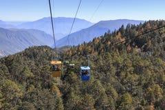 Kabelbil på förgrund med några inre turister och Jade Dragon Snow Mountain på förgrund Jade Dragon Snow Mountain, i Y Arkivbilder