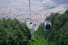 Kabelbilar som in går upp till berget, gröna kullar arkivbild