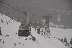 Kabelbilen stiger ned i snön Arkivfoton
