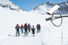 Kabeltelevisie-Camera die op sneeuwberg werken met mensen die in bac wandelen Royalty-vrije Stock Fotografie