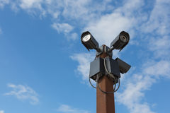 Kabeltelevisie-veiligheid drie camera's tegen op de hemel Stock Foto