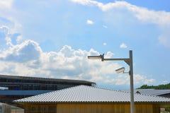 Kabeltelevisie-veiligheidscamera in de toegewezen huisvesting met wolk en blauwe hemel stock afbeelding