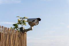 Kabeltelevisie-veiligheidscamera op tuinomheining met blauwe hemel op achtergrond Stock Afbeeldingen