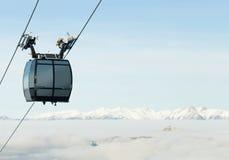 Kabelwagencabine het uitgaan boven de wolken aan zeer hoogste van een berg bij een skitoevlucht Stock Fotografie