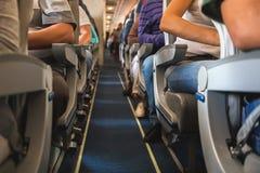 Kabin av flygplanet med passagerare på platser Arkivbild
