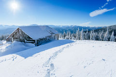 Kabin i bergen i vinter arkivbild