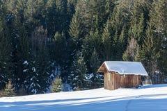 Kabin i vintern med snö på en kulle i skogen Royaltyfria Foton