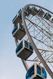 Kabinen von Ferris Wheel und von blauem Himmel auf Hintergrund Stockfoto