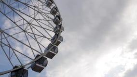 Kabiner Ferris Wheel som roterar på en bakgrund för molnig himmel lager videofilmer