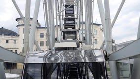 Kabiner Ferris Wheel som roterar på en bakgrund för molnig himmel arkivfilmer