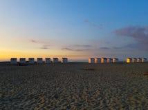 Kabiner på stranden på solnedgången arkivbild
