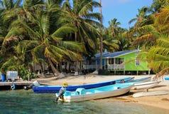 Kabiner på styltor på den lilla ön av tobak Caye, Belize Royaltyfri Fotografi
