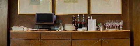 Kabinet met kasregister, schotels en flessen in het restaurant Stock Afbeelding