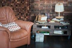 Kabinett i vindstilen Vardagsrum i ekostyle Bruna soffor, böcker och trästrålar arkivfoto