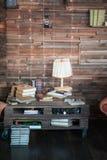 Kabinett i vindstilen Vardagsrum i ekostyle Bruna soffor, böcker och trästrålar royaltyfri fotografi