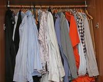 Kabinett mit den Kleidern und Hemden, die vom Garderobenständer hängen Lizenzfreies Stockfoto