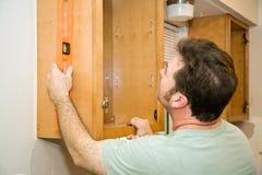 Kabinette installieren - ausrichtend Stockfotos