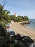 Kabiny na plaży prowadzi latarnia morska Fotografia Royalty Free