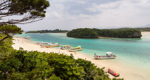 Kabira Bay, Ishigaki Island, Japan. KABIRA, JAPAN - APRIL 6 : Glass-bottomed tourist boats line the sandy beach at Kabira Bay, Ishigaki Island, Okinawa Royalty Free Stock Photography