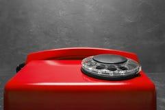 Kabla naziemnego czerwony telefon na szarym ściennym tle Zdjęcie Stock