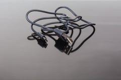 Kabla USB till mikro-USB på en mörk reflekterande yttersida arkivbild