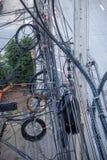 Kablar tilltrasslade på den elektriska polen royaltyfri bild