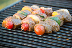 Kabobs on the grill. Beef and vegetable kabobs on a skewer cooking on the grill Royalty Free Stock Images