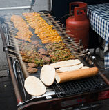 Kabobs on large grill. Kabobs on skewers and other foods cooking on a large outdoor grill stock image
