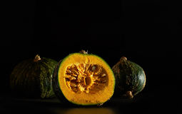 Kabocha pumpkins over a black background. Royalty Free Stock Photography