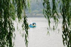Kaczki łódź na jeziorze poza zieleni drzewni liście Zdjęcie Royalty Free