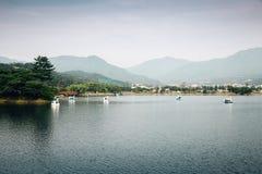 Kaczki łódź na jeziorze z górą Zdjęcia Royalty Free