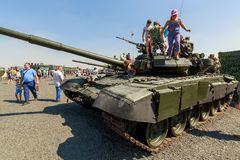 Young visitors inspect of the tank T-90A. KADAMOVSKIY TRAINING GROUND, ROSTOV REGION, RUSSIA, 26 AUGUST 2017: International military technical forum ARMY-2017 Stock Image