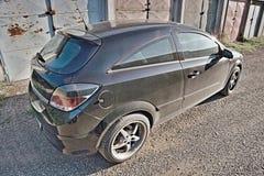 2016/07/09 Kadan, Tsjechische republiek - zwarte die auto tussen garages wordt geparkeerd stock afbeeldingen