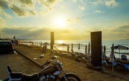 Kade met geparkeerde auto's en motorfiets in de voorgrond Zonsondergangzon op de achtergrond van wolken, zandig strand met sunbed stock afbeelding