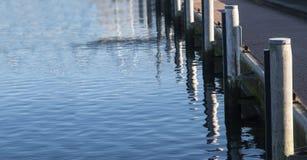 Kadekust bij de jachthavenhaven met houten meerpalen en blauwe overzees, Royalty-vrije Stock Fotografie