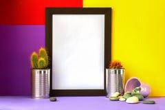 Kader met cactussen in metaalblikken op lichte violette vloer en heldere rode gele en violette achtergrond voor copyspace royalty-vrije stock foto's