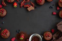 Kader met chocolademuffins, chocoladerepen, cacao en bessen op donkere houten achtergrond Hoogste mening Vlak leg royalty-vrije stock afbeelding