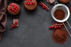 Kader met chocolademuffins, chocoladerepen, cacao en bessen op donkere houten achtergrond Hoogste mening Vlak leg stock foto