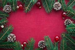 Kader met Kerstmisboom en ornamenten op rode canvasachtergrond Vrolijke Kerstkaart Royalty-vrije Stock Foto