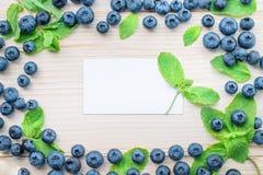 Kader van bosbessen en muntbladeren op een lichte houten lijst Gezond ontbijt met essentiële vitaminen Stock Foto's