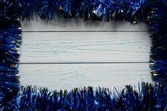 Kader van een blauwe Kerstmisslinger Houten witte achtergrond Royalty-vrije Stock Afbeelding