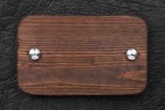 Kader van houten die raad wordt, met ijzerklinknagels aan zwart leer wordt vastgemaakt gemaakt dat royalty-vrije stock foto's