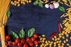 Kader van Italiaans traditioneel voedsel, kruiden en ingrediënten voor het koken als basilicum, kersentomaten, knoflook en divers royalty-vrije stock foto