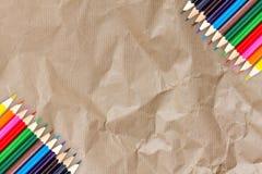 Kader van Kleurenpotloden op het Kringloopdocument van de Kartontextuur backg Stock Foto's