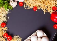 Kader van macaroni en groenten op de zwarte achtergrond De ruimte van het exemplaar Hoogste mening stock afbeelding
