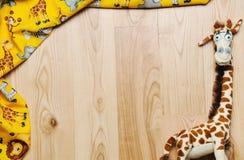 Kader van materiaal en speelgoed voor pasgeboren baby op houten achtergrond Stock Fotografie
