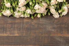 Kader van mooie minirozen op een bruine houten lijst Mooie bloemen vakantie Hoogste mening stock afbeeldingen