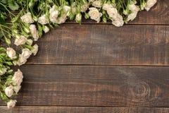 Kader van mooie minirozen op een bruine houten lijst Mooie bloemen vakantie Hoogste mening royalty-vrije stock foto
