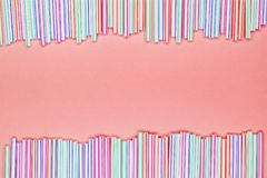 Kader van multicolored gestreept plastic stro op een koraal roze achtergrond met exemplaarruimte Recyclerend afval stock afbeeldingen